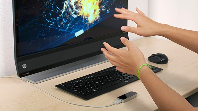 The Leap Motion Controller, seen here beside the keyboard, lets you control apps by moving your hands in the air.