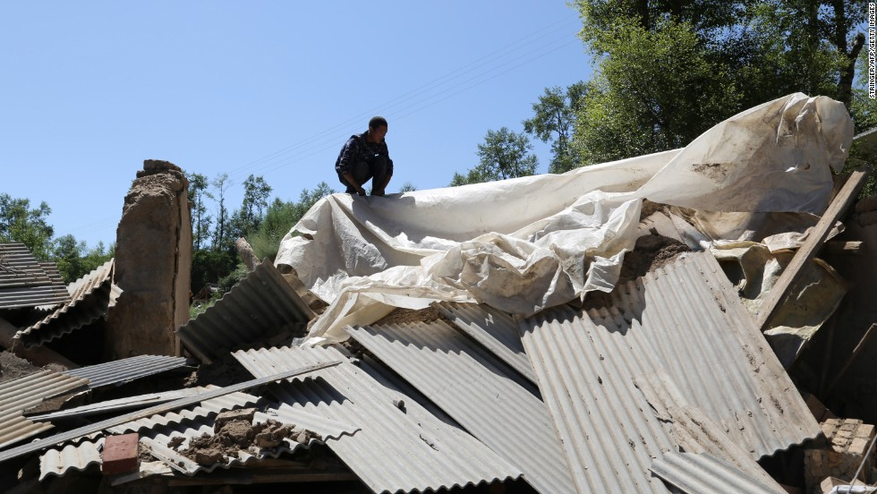 A man checks out a damaged house in Hetuo township in Dingxi in China's Gansu Province on Monday, July 22.