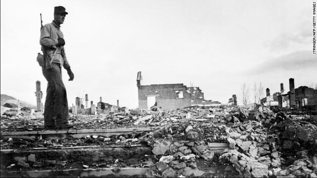 An American soldier walks around the rubble of Hamhung, Korea, circa 1950.