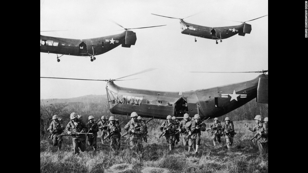 U.S. troops emerge from helicopters onto an open field, circa 1953.