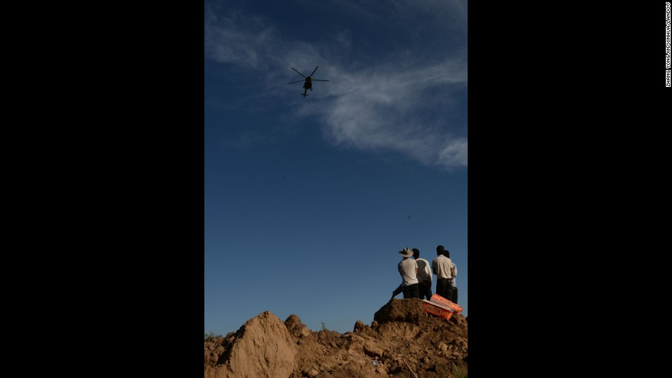 A helicopter airdrops relief supplies above Yongguang on July 22 as villagers wait on the ground.