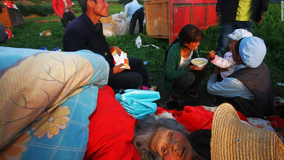 "JULY 23 - MAJIAGOU, CHINA: Survivors of a deadly earthquake in northwest China's Gansu province eat instant noodles in a clearing after their homes were damaged. At least <a href=""http://cnn.com/2013/07/21/world/asia/china-quake/index.html?hpt=ias_c2"">89 people died and 600 others were injured</a> in the quake, according to state media."