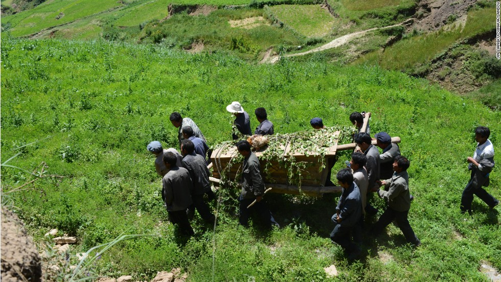 People carry a coffin July 23 during a funeral for an 84-year-old villager from Lalu who was killed in the earthquake. The death toll has risen to 94, local authorities said Tuesday.
