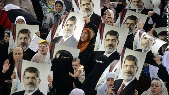 Female Egyptian supporters of the Muslim Brotherhood hold up portraits of Egypt's ousted president Mohamed Morsi during a rally in Cairo on July 21, 2013.