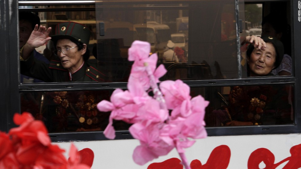 Veterans of the Korean War wave at the crowd as they leave by bus after arriving at the Pyongyang railway station Tuesday, July 23.