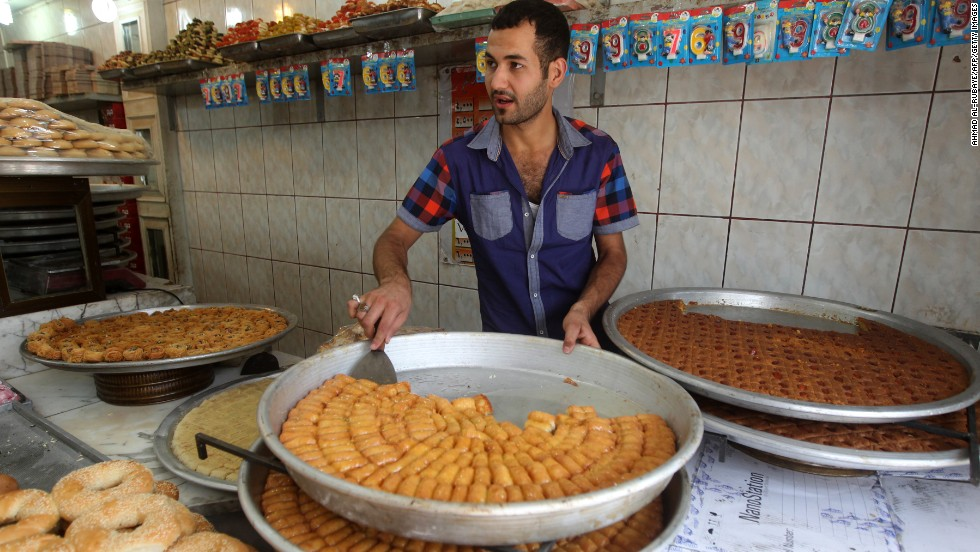 In Baghdad City, a man prepares to serve sweets as dusk approaches on Wednesday, July 24.