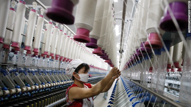 A laborer is seen working in a textile factory in Huaibei, in north China's Anhui province on July 24, 2013. China's manufacturing activity contracted to a 11-month low in July, an HSBC survey showed on July 24, the first evidence of the Asian economic giant losing further momentum in the third quarter. CHINA OUT AFP PHOTO (Photo credit should read STR/AFP/Getty Images)