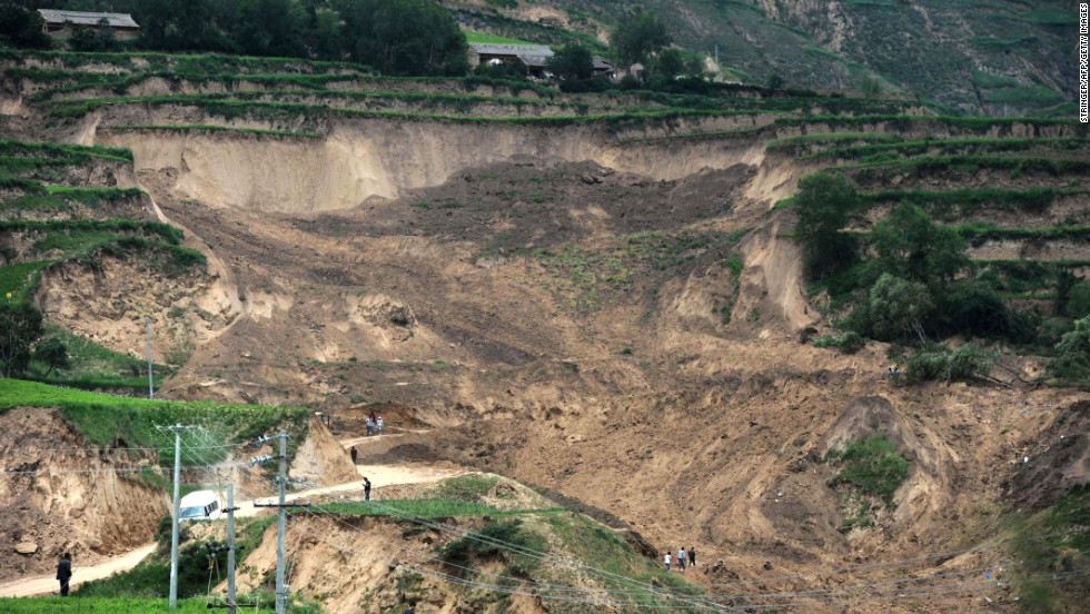 People look at damage on July 24 from a landslide triggered by Monday's earthquake.