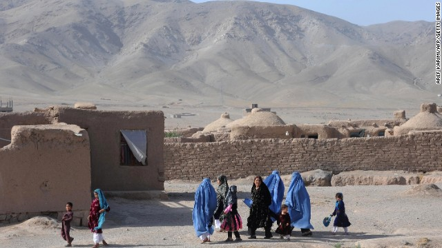 Afghan women, with their children, walk on the outskirts of Herat on June 11, 2013.