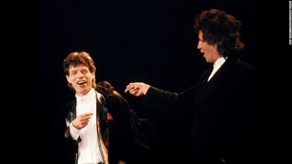 The Rolling Stones are inducted into the Rock and Roll Hall of Fame a year later. Mick Jagger and Keith Richards take the stage in 1989.