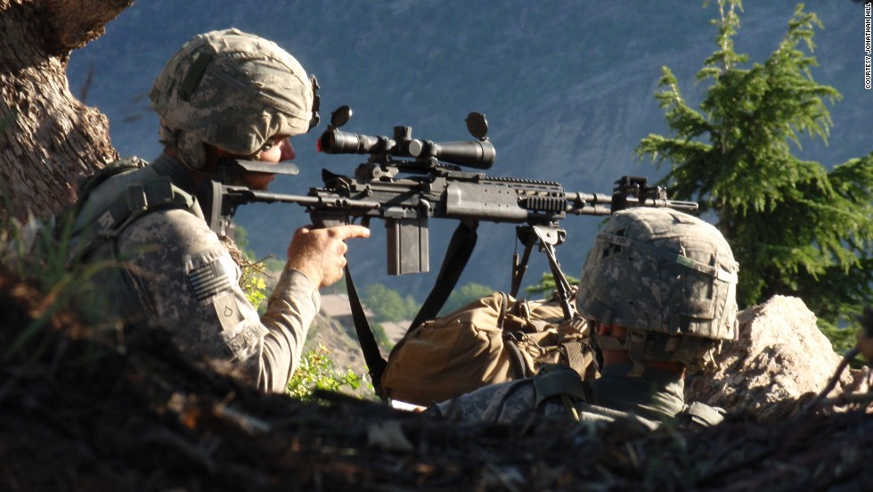 Carter with Spc. John Adams on their first patrol in Afghanistan. They are observing the Village of Kamdesh from a ridgeline between Observation Post Fritsche and the village.