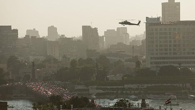 CAIRO, EGYPT - JULY 26: An Egyptian Army Apache helicopter flies over a crowd of pro-military demonstrators at Tahrir Square on July 26, 2013 in Cairo, Egypt. Protesters gathered to show support of the overthrow of Egyptian President Mohammed Morsi by the Egyptian military on July 3rd. General Ahmed Fattah al-Sissi, Egypt's Chief of the Armed Forces, called for mass anti-Morsi protests across Egypt on against 'violence and terrorism'. Egyptian authorities took their first legal steps against deposed President Morsi on Friday, charging Morsi with allegations of espionage and murder during his year in power. (Photo by Ed Giles/Getty Images).