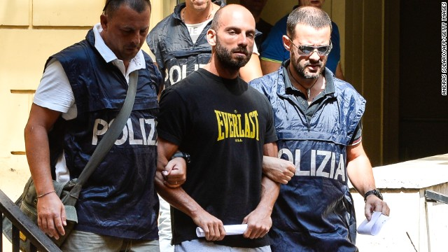Police officers in central Rome lead away one of dozens arrested for organised crime in Ostia on July 26, 2013.