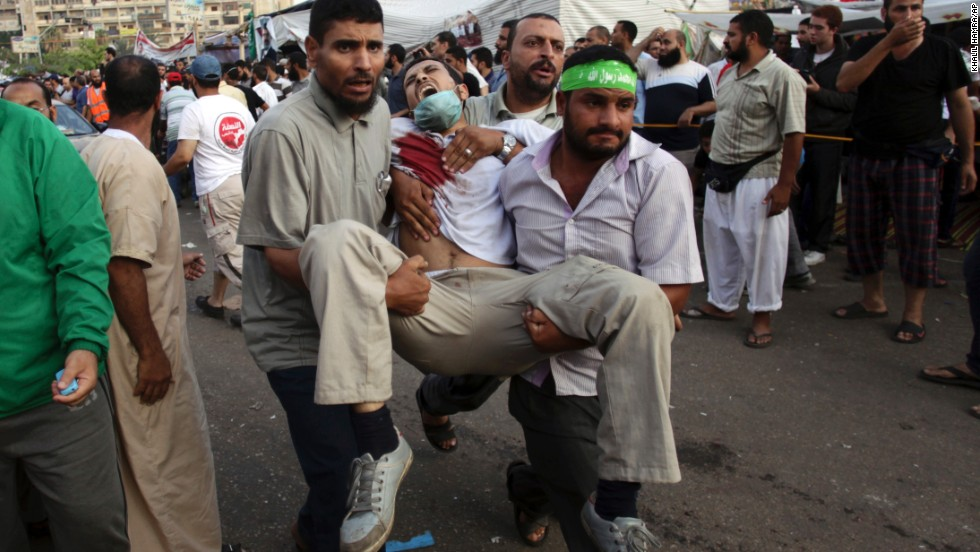 Supporters of Morsy carry an injured man to a field hospital amid clashes with security forces in Cairo on July 27.