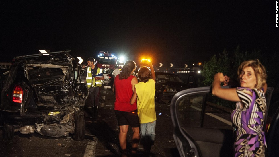 Emergency workers and onlookers stand among damaged cars at the scene of the accident.