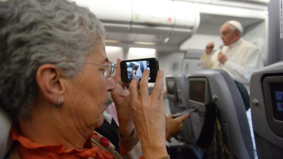"A journalist takes a picture of Pope Francis during the press conference on the flight back to Italy. The pope said the role of women in the church should be deeper, but he brushed aside the possibility of women being ordained as priests. ""The church says no. That door is closed."""