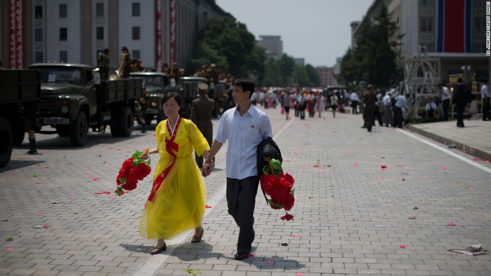 A couple walks through Kim Il Sung Square after a parade in Pyongyang on July 27.