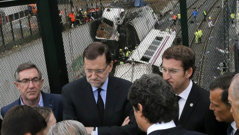 Spanish Prime Minister Mariano Rajoy, second from left, and Galicia's regional President Alberto Nunez Feijoo, right, visit the site of the derailment on Friday, July 26.