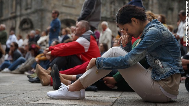 A woman watches the memorial service for the victims of the crash, at Santiago de Compostela Cathedral on July 29, 2013.
