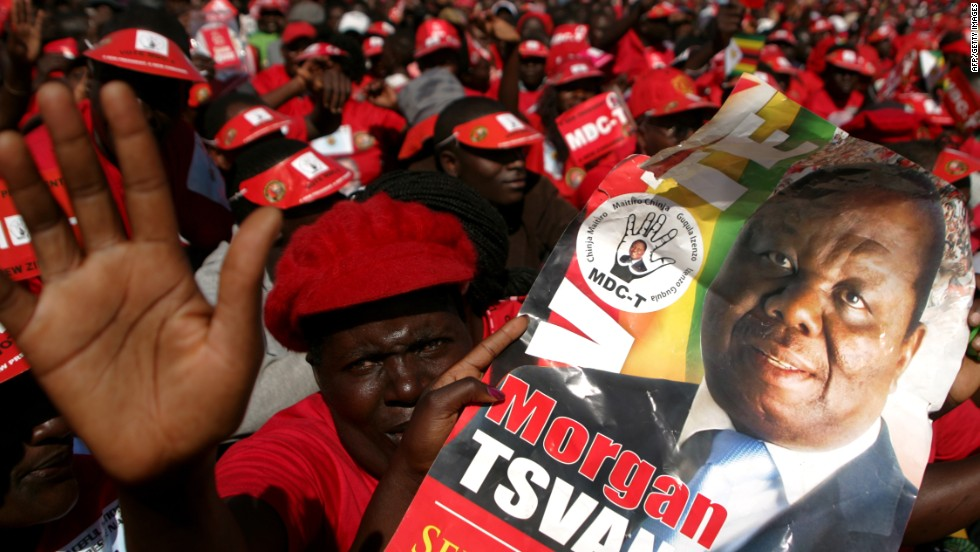 Supporters of the Movement for Democratic Change presidential candidate Morgan Tsvangirai hold his portrait as they attend the final campaign rally 'Cross Over' on July 29 in Harare.