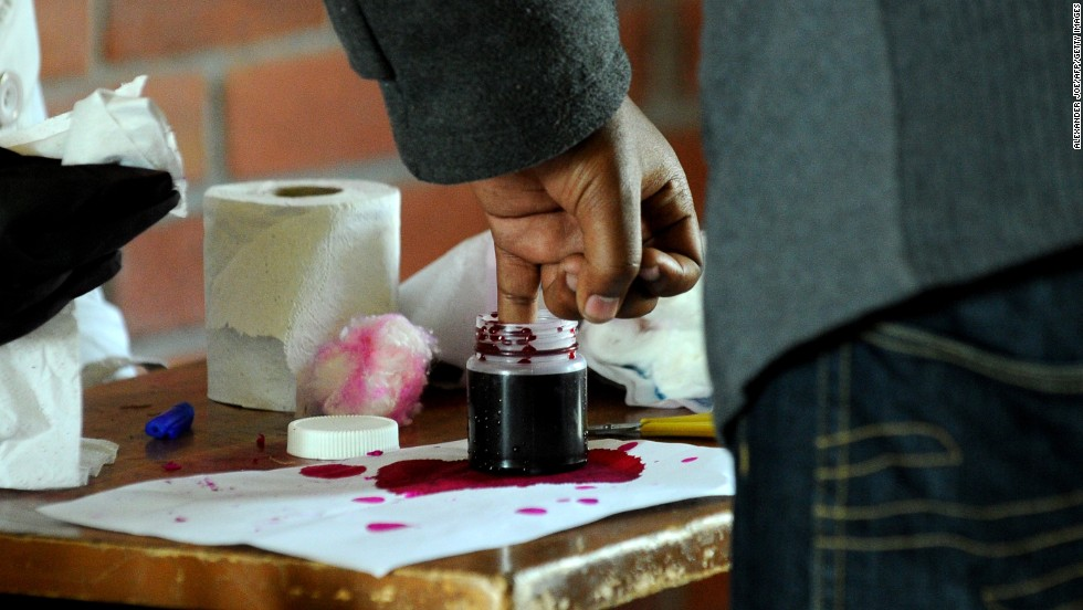 A man places his finger in a bottle of ink to stop fraud before voting at a polling station at a school in Harare.