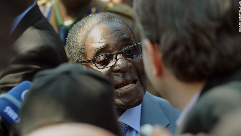Zimbabwe President Robert Mugabe answers journalists questions after voting at a polling station at a school in Harare.
