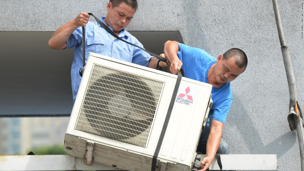 Workers install an air conditioning unit in a food stall in Shanghai on July 2.