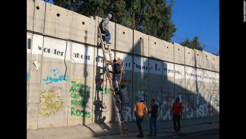 Palestinians use a ladder to climb over the separation barrier with Israel in Al-Ram on their way to pray at the al-Aqsa Mosque in Jerusalem, August 2.
