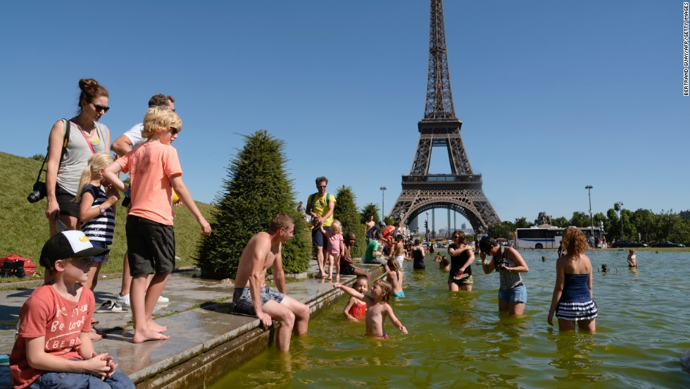 People sunbath on lawns near the Eiffel Tower in Paris, on August 1.