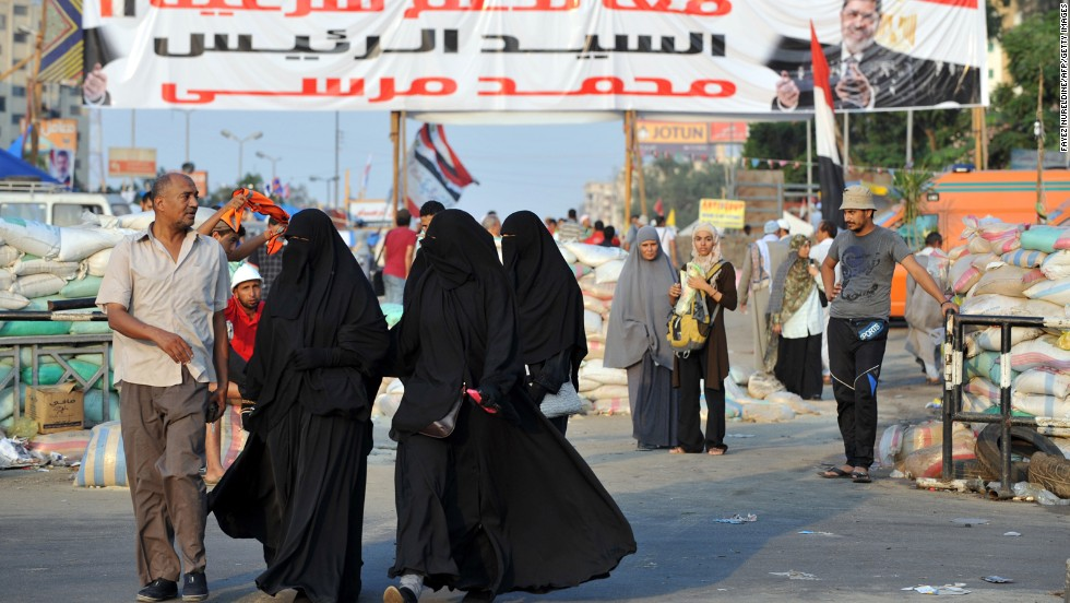 Morsy supporters walk past makeshift roadblocks at Rabaa al-Adawiya Square in Cairo on Saturday, August 3. Security forces set up the roadblocks outside the square, allowing people to leave but not enter, as they attempt to break up camps set up during ongoing protests over Morsy's ouster.