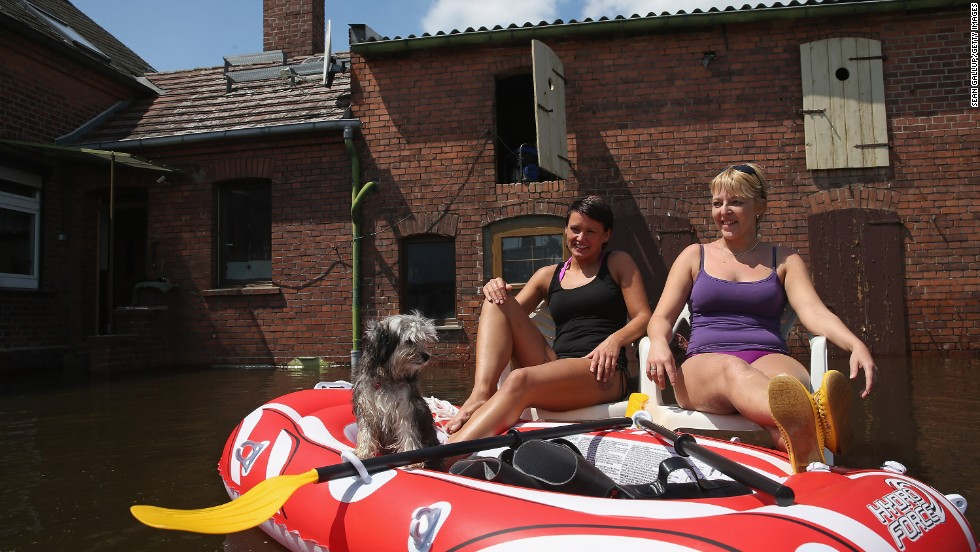 Friends Stephanie, center, and Sandra, right, made the best of a flood in Elster, Germany, with Stephanie's dog Chewbacca.
