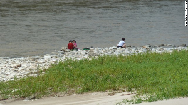 A North Korean family crouches by the river in Hyangsan, three hours from Pyongyang.