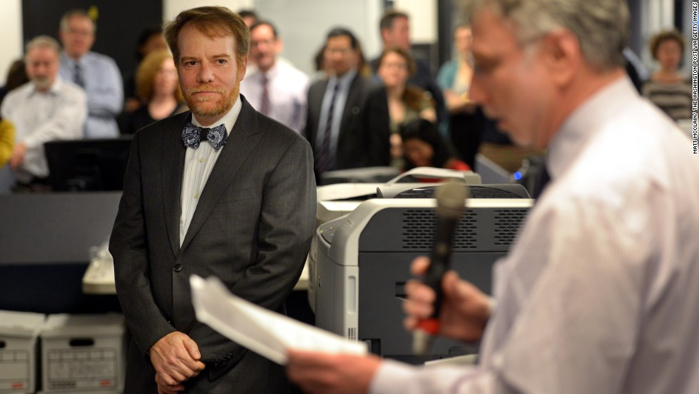Art critic Philip Kennicott, left, listens to executive editor Martin Baron in the Washington Post newsroom after Kennicott was announced as a Pulizter Prize winner on April 15, 2013. Over the years the paper has earnerd dozens of Pulitzers, journalism's most prestigious award.