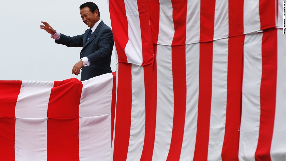Taro Aso, Japan's deputy prime minister and finance minister, acknowledges the crowd during the launching ceremony.