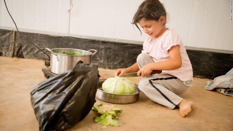A young girl helps prepare the evening meal, <em>iftar</em>, with her family in Za'atari refugee camp.