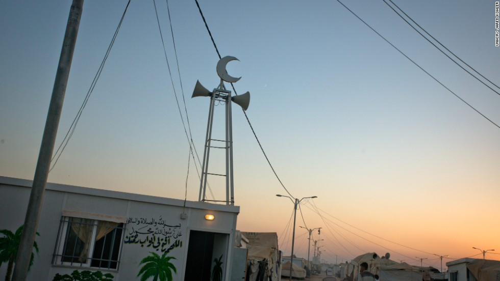 The sun sets over Za'atari in northern Jordan, where Syrian refugees pass one of the many makeshift mosques that have mushroomed in the sprawling refugee camp. It is home to around 145,000 people.