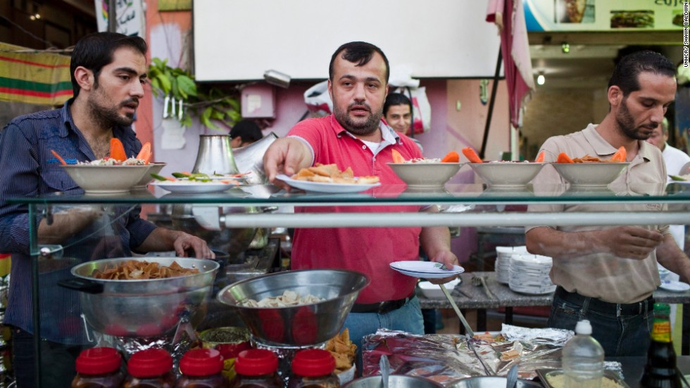 "Syrian chef, Galal (center), prepares the evening iftar meal during Ramadan at the busy Bab Elhara Restaurant in Cairo. He fled to Egypt a month ago with his wife and two children.  <br />""I was away from Syria for eight years of my own free will, but now I'm away forcibly. As soon as things calm down, I will go back home,"" he said."