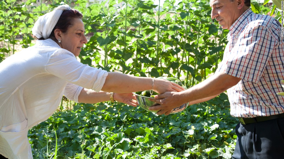 Foddiye (left) and her husband currently host seven Syrian refugee families rent-free on their land in the Bekaa Valley in Lebanon. Here she picks vegetables from her garden for Iftar with Abou (right), a Syrian refugee.
