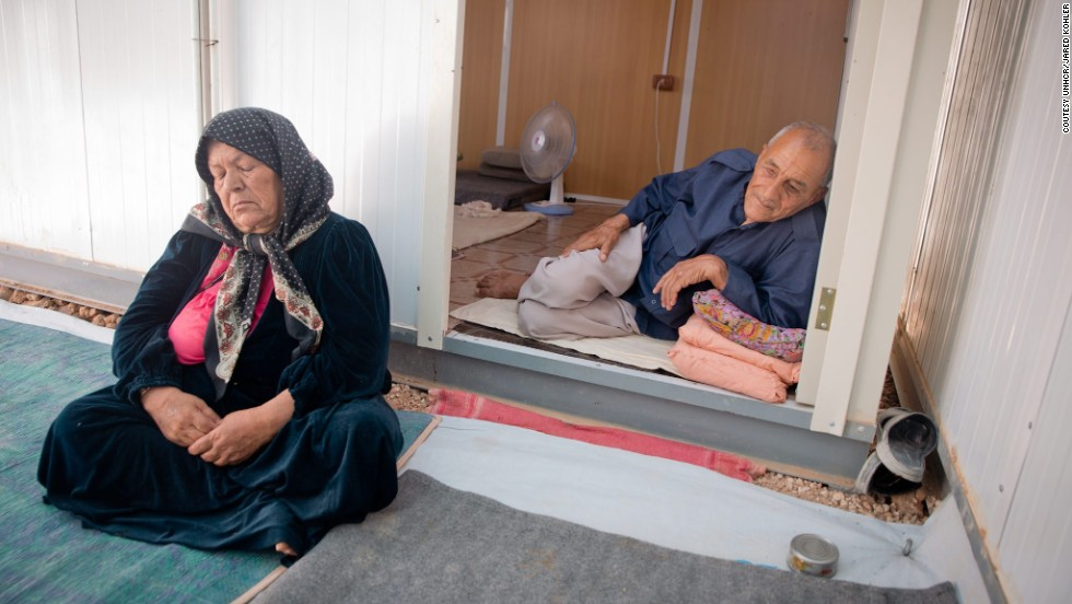 An elderly couple sits outside their caravan on a hot afternoon during Ramadan in Za'atari refugee camp in Jordan. The heat is challenging for the elderly, but many fast anyway.