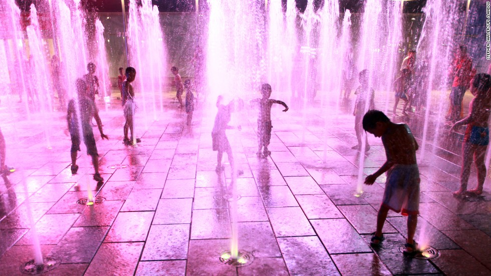 Children stay cool at a public water fountain at a shopping mall in Beijing on August 9.