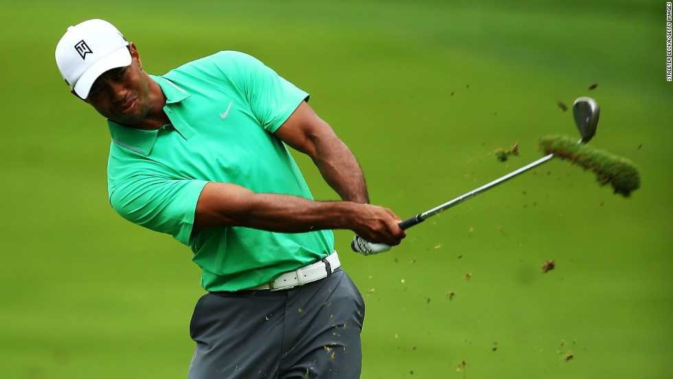 Tiger Woods takes a big divot as he plays his approach shot to the second hole at Oak Hill on his way to a 70.