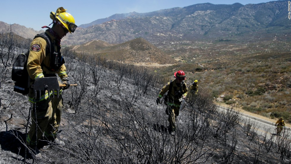 Firefighters look for hot spots as they walk through a scorched area near Banning on August 9.