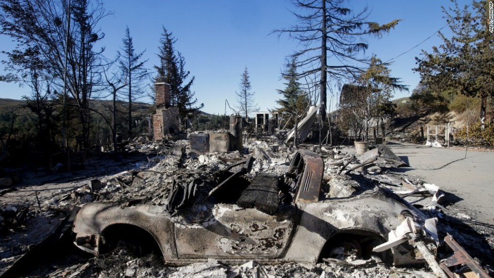 The remains of a car and a home destroyed by the wildfire near Banning on August 9.