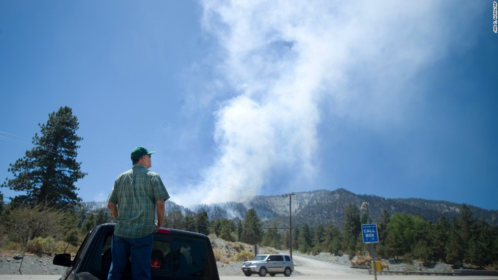 Ruben Gomez watches air crews battle the fire on August 9, near Wrightwood, California.