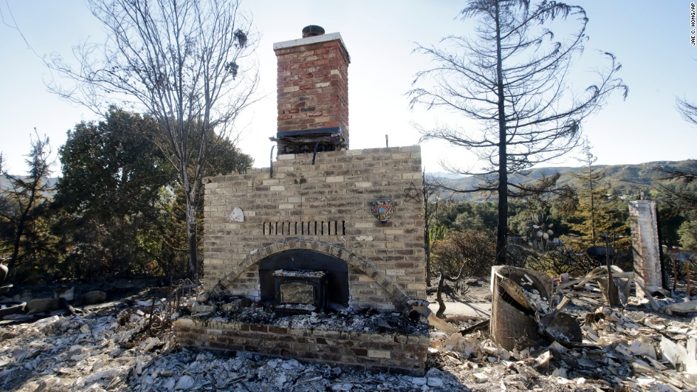 A brick fireplace and chimney are all that remain of a home destroyed by wildfire near Banning on August 9.