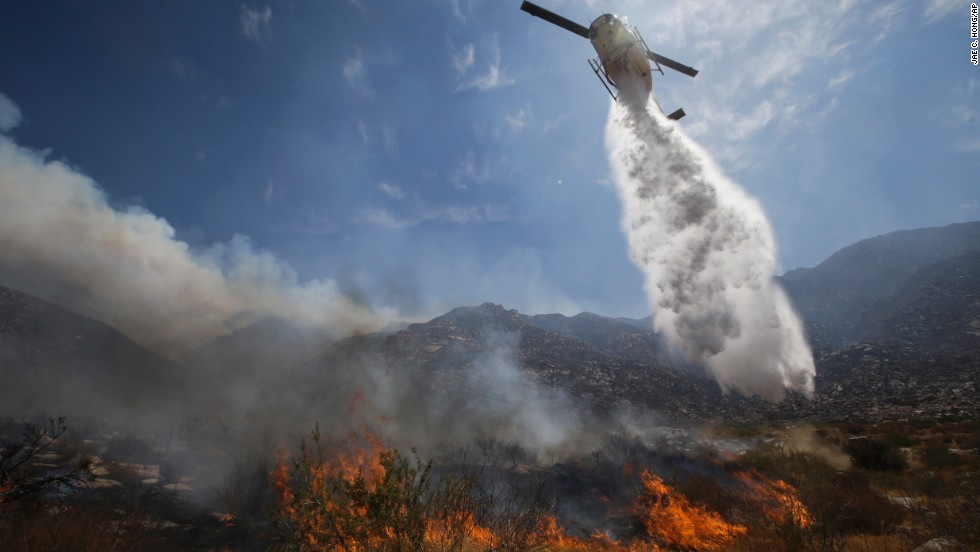 A helipcopter drops water over a wildfire on Thursday, August 8, near Cabazon, California.