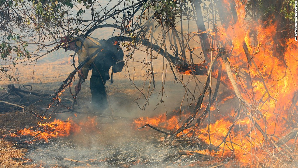 A firefighter with the Vista Grande Hot Shots works on setting a perimeter at the Twin Pines Ranch, on August 8, near Banning.