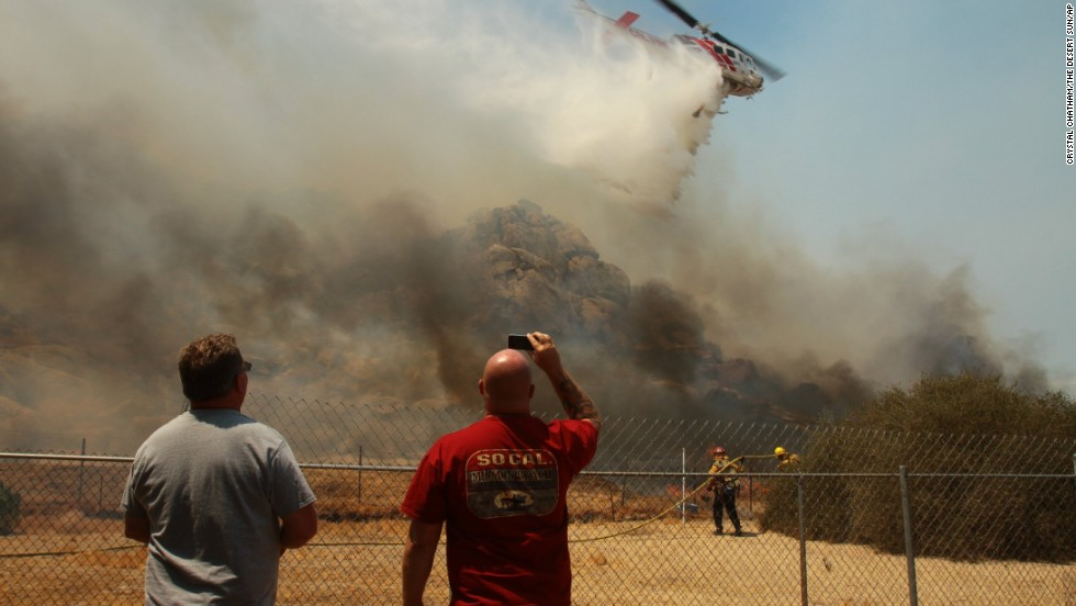 Terry Tincher, left, and his brother Leonard watch a helicopter work to put out flames near their grandmother's home on August 8 in Cabazon, California.