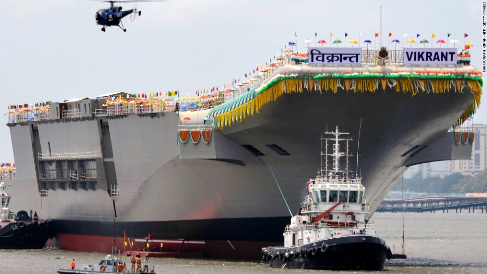 Tugboats guide aircraft carrier INS Vikrant as it leaves the Cochin Shipyard after the launch ceremony in Kochi, India, on Monday, August 12, 2013. India's carrier is one-third the size of U.S. Navy's Nimitz class carriers.