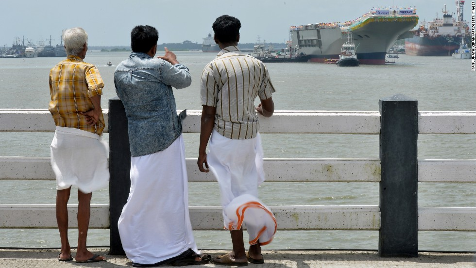 People watch as the INS Vikrant leaves Cochin Shipyard on August 12.